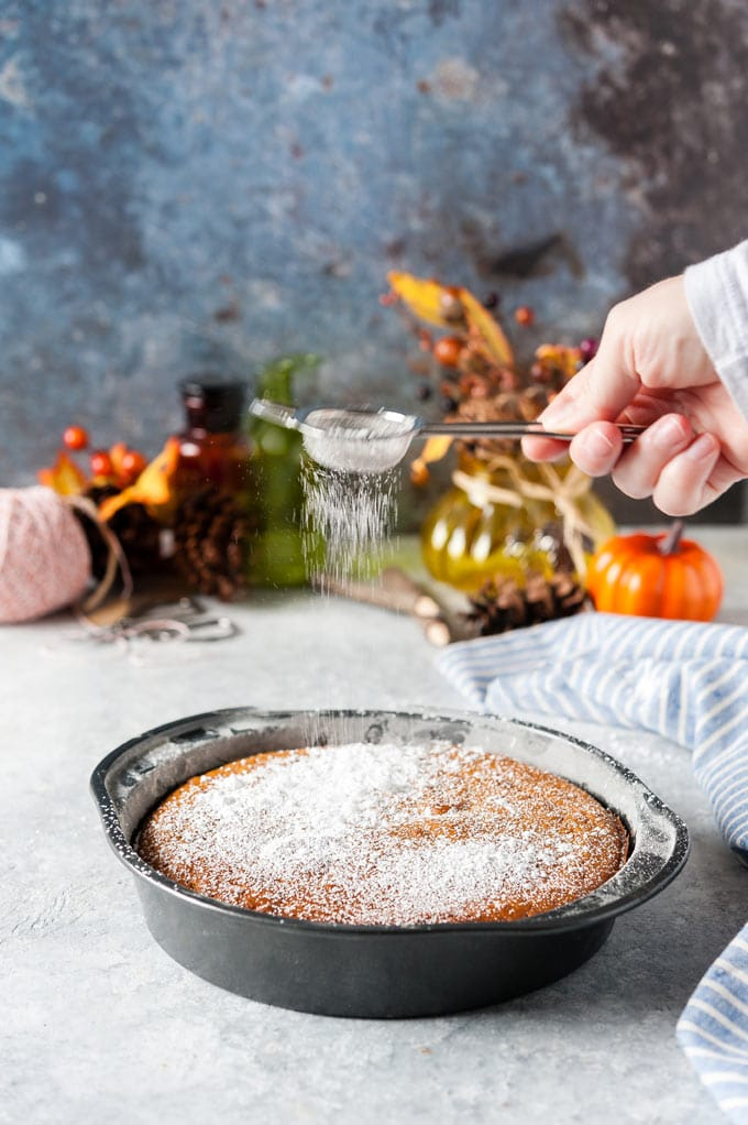 Icing sugar sifting over pumpkin cake.