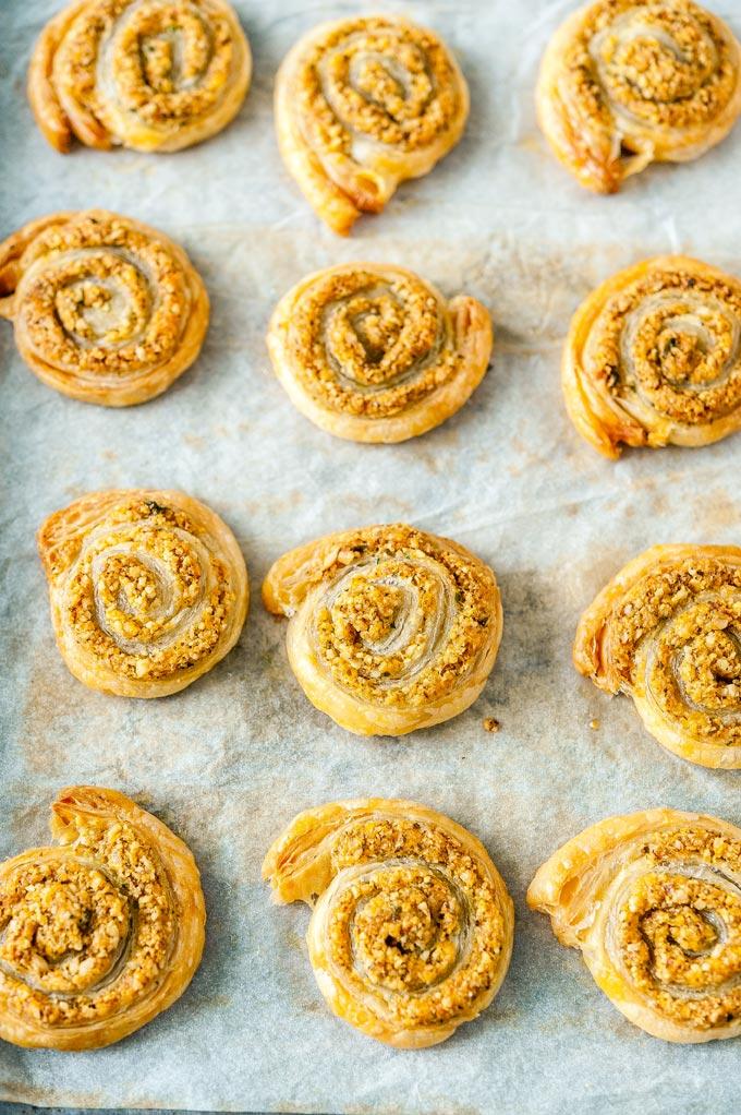 Baked cheesy pinwheels on a sheet pan.
