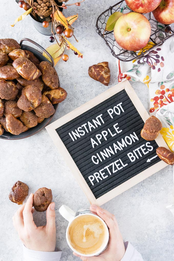 Letter board that says Instant Pot Apple Cinnamon Pretzel Bites and hands dholding a cup of coffee.