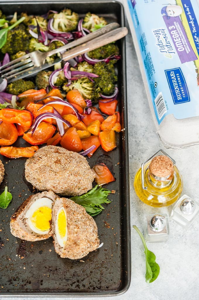 Baked scotch eggs with vegetables on a sheet pan.