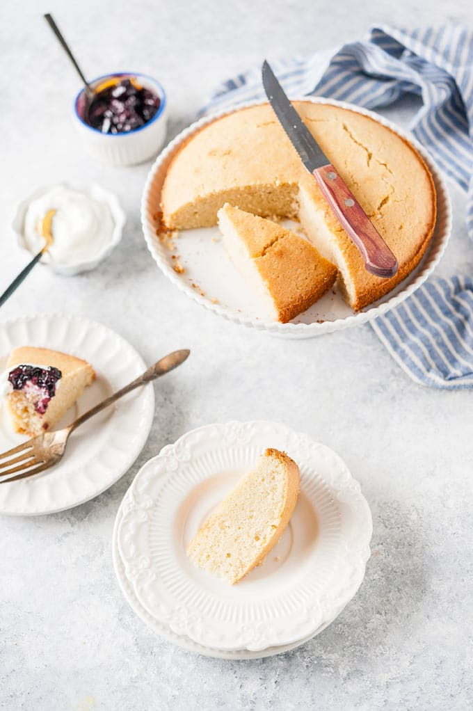 Almond cake on a plate with a few pieces cut out.