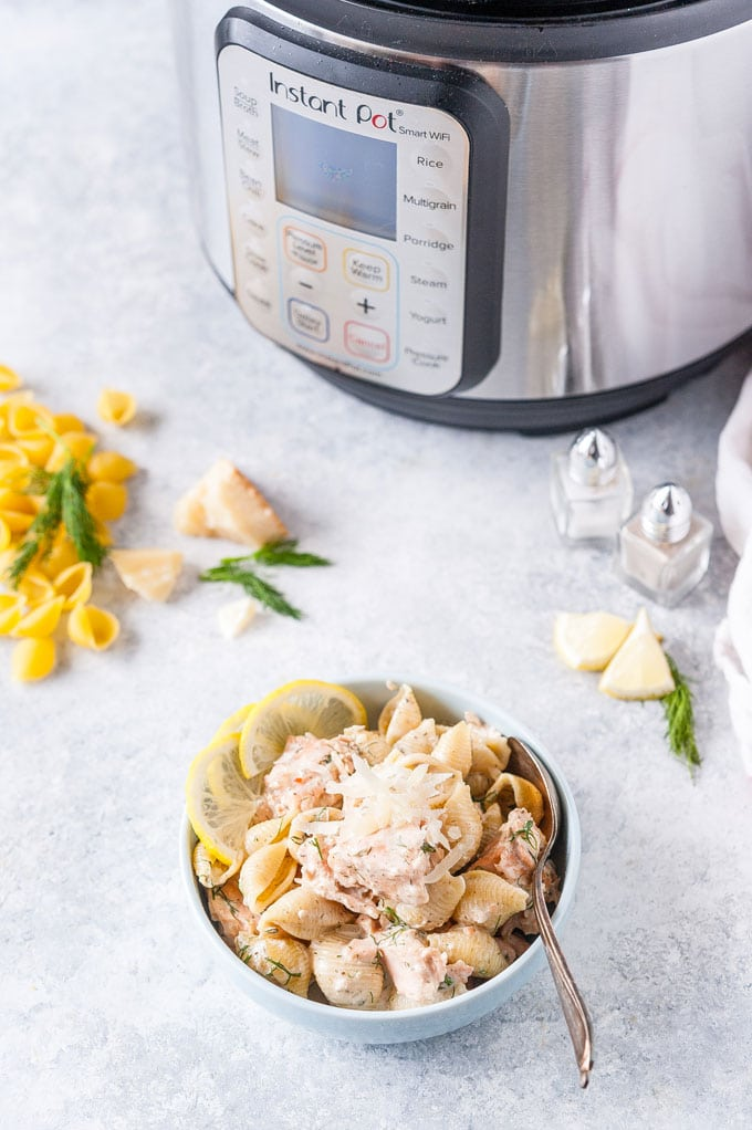 Bowl of Creamy Salmon Pasta with Instant Pot in the background.