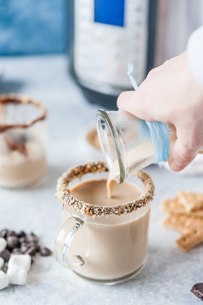 Hand pouring latte into a mug.