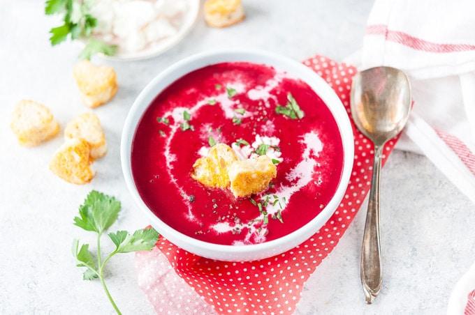Closeup of a bowl of creamy beet soup.