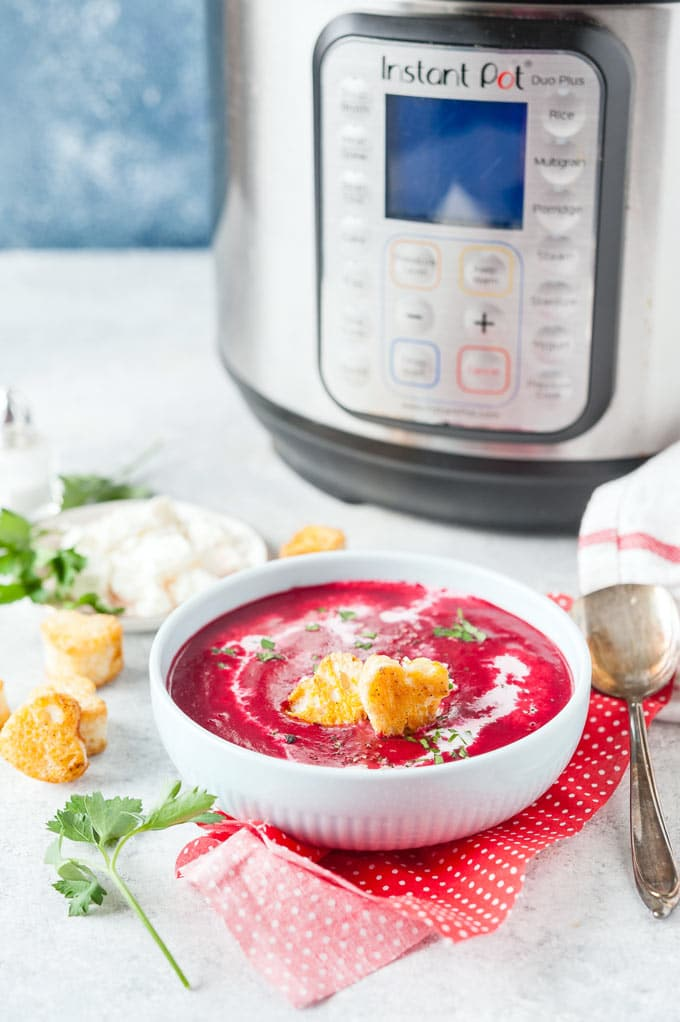 Bowl of beet soup with instant pot in the background.