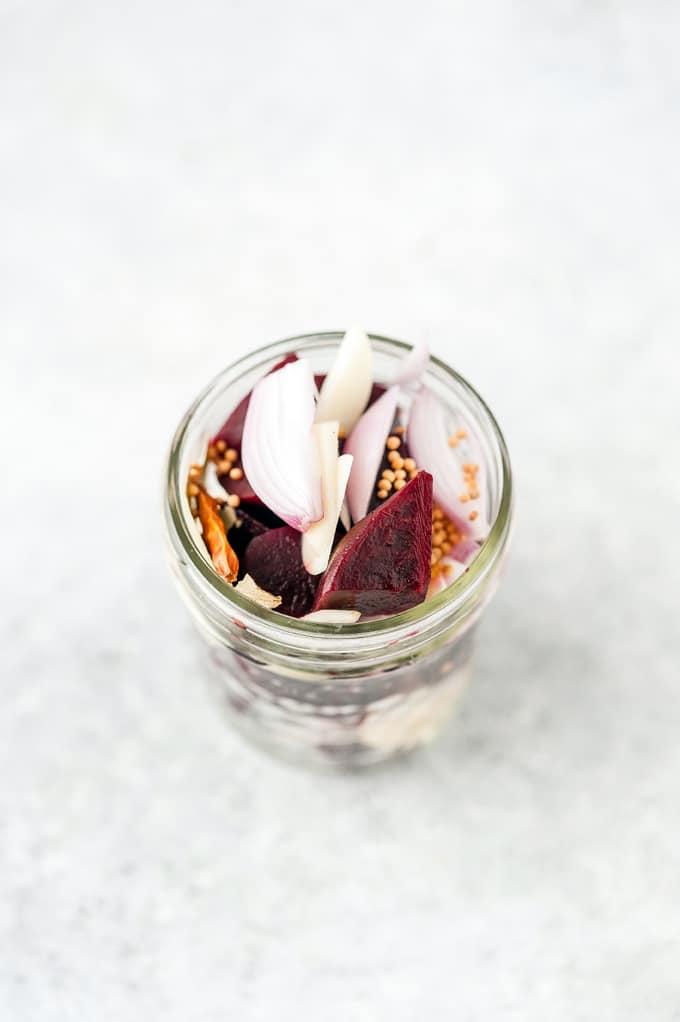 Beets, shallots, and garlic layered in a jar.