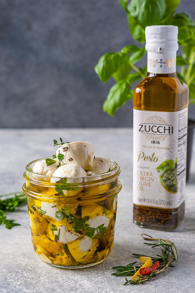 Jar with marinated bocconcini and the bottle of olive oil behind it.