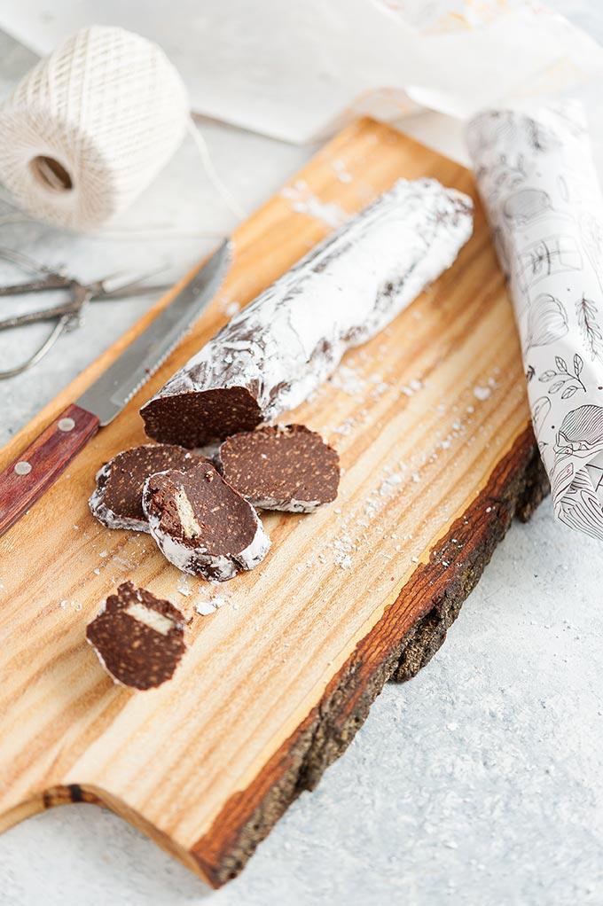 Chocolate salami sliced on a cutting board.