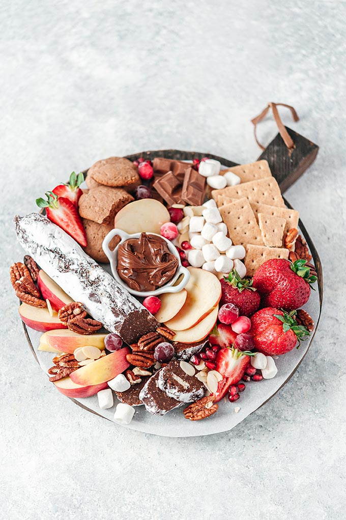 Top down view of a dessert board. It is filled with cookies, fruits, and chocolates.