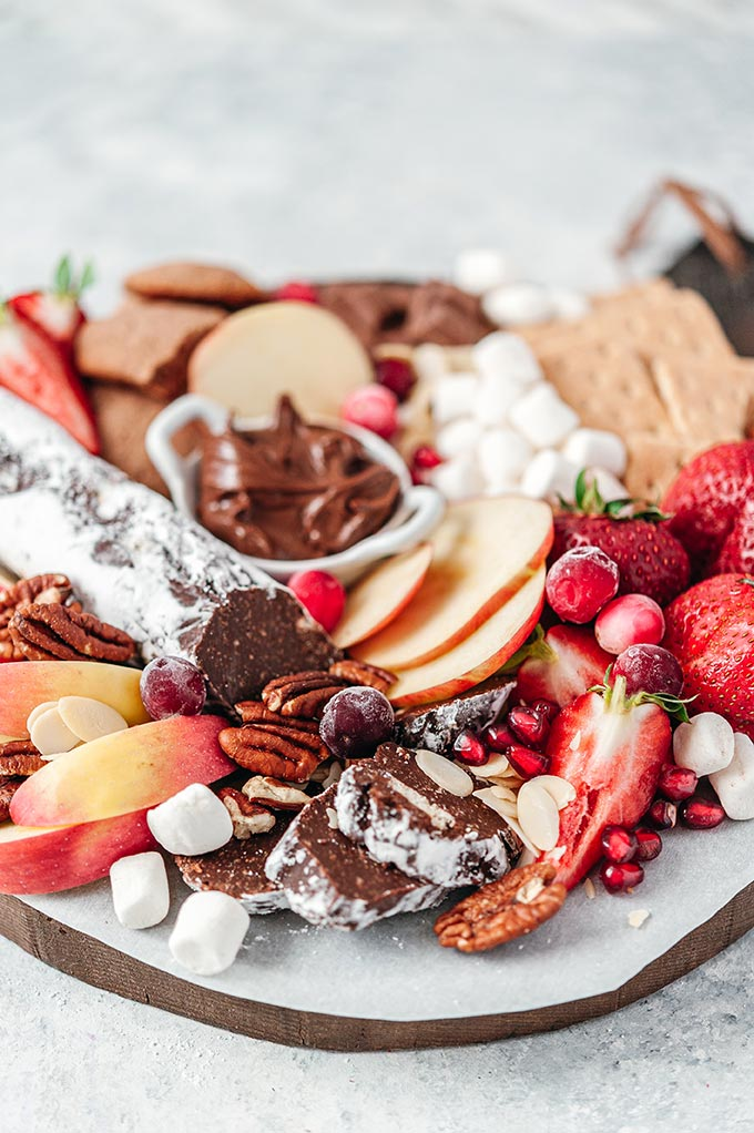 Dessert board with fruit, sweets, and chocolate salami.