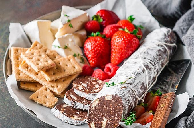 Plate with chocolate salami, crackers, cheese, and strawberries.